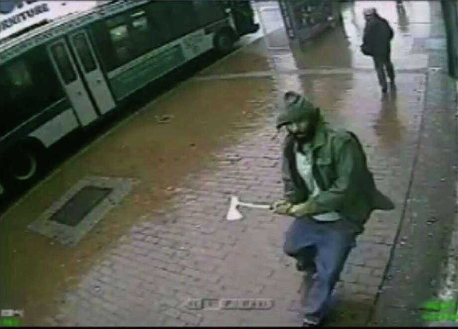 In this frame grab taken from video provided by the New York Police Department, an unidentified man approaches New York City police officers with a hatchet, Thursday, Oct. 23, 2014, in the Queens borough of New York. The man injured two with the hatchet before the other officers shot and killed him, police said. A bystander was wounded in the gunfire. Investigators were still trying to confirm the identity of the assailant and determine a motive. (AP Photo/New York Police Department) Photo: AP / New York Police Department