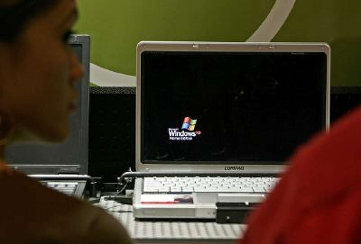 A customer looks at a laptop that is using Microsoft Windows XP operating system software at a CompUSA store March 22, 2006 in San Francisco, California.