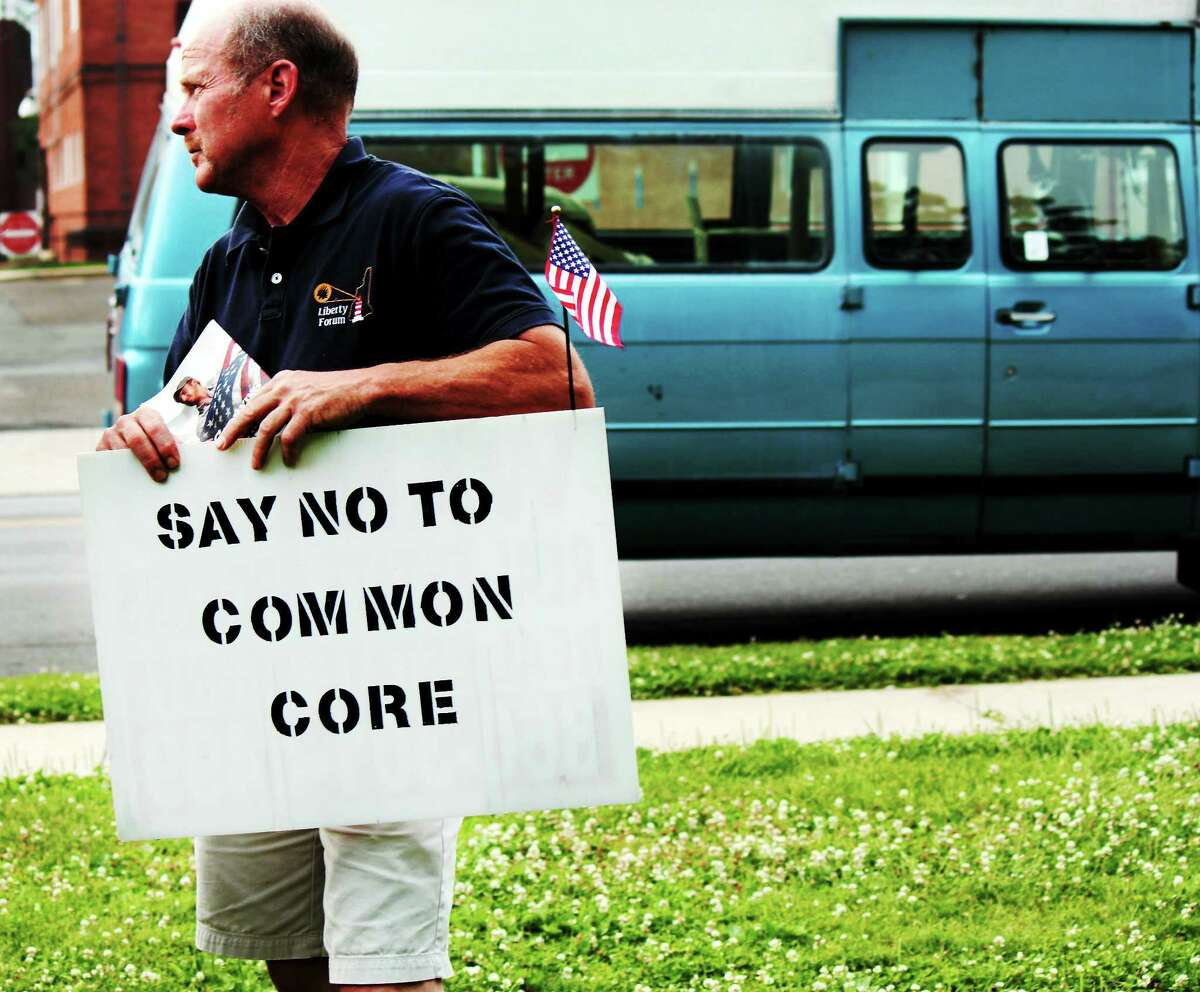 Patrick Lacy from East Haddam stands in front of West Haven City Hall protesting against the Common Core Curriculum.