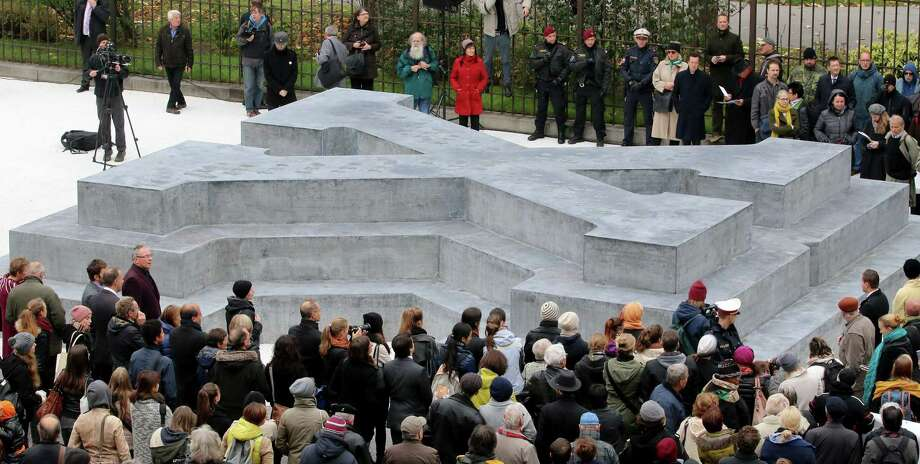 People surround a memorial dedicated to deserters of the Nazi Wehrmacht troops and victims of their military justice during its unveiling ceremony in downtown Vienna, Austria, Friday, Oct. 24, 2014. The memorial is located in front of the presidential office in the Hofburg palace and the federal chancellery. (AP Photo/Ronald Zak) Photo: AP / AP