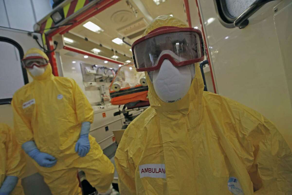 The medical team of the Paris emergency unit wearing their protective suits wait in front of an ambulance for a training session to take care of suspected Ebola cases during the presentation to the press, in Paris, Friday, Oct. 24, 2014. (AP Photo/Francois Mori)