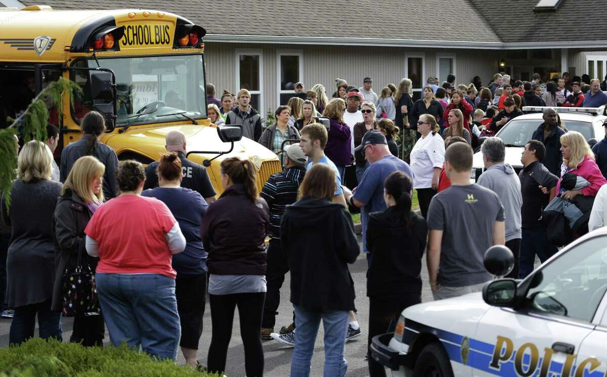 Parents crowd around busses that took students to a church Friday following a shooting at Marysville Pilchuck High School in Marysville, Wash.