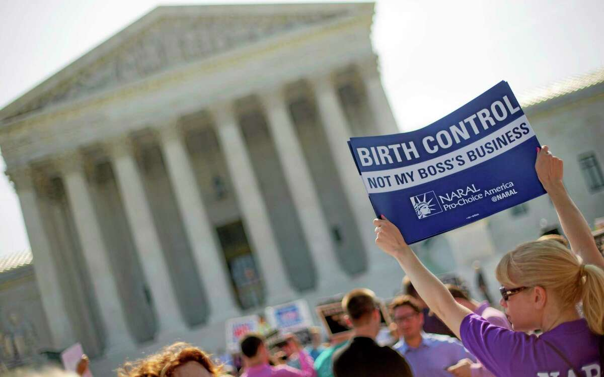 A demonstrator holds up a sign outside the Supreme Court in Washington, Monday, June 30, 2014. The Supreme Court is poised to deliver its verdict in a case that weighs the religious rights of employers and the right of women to the birth control of their choice. (AP Photo/Pablo Martinez Monsivais)