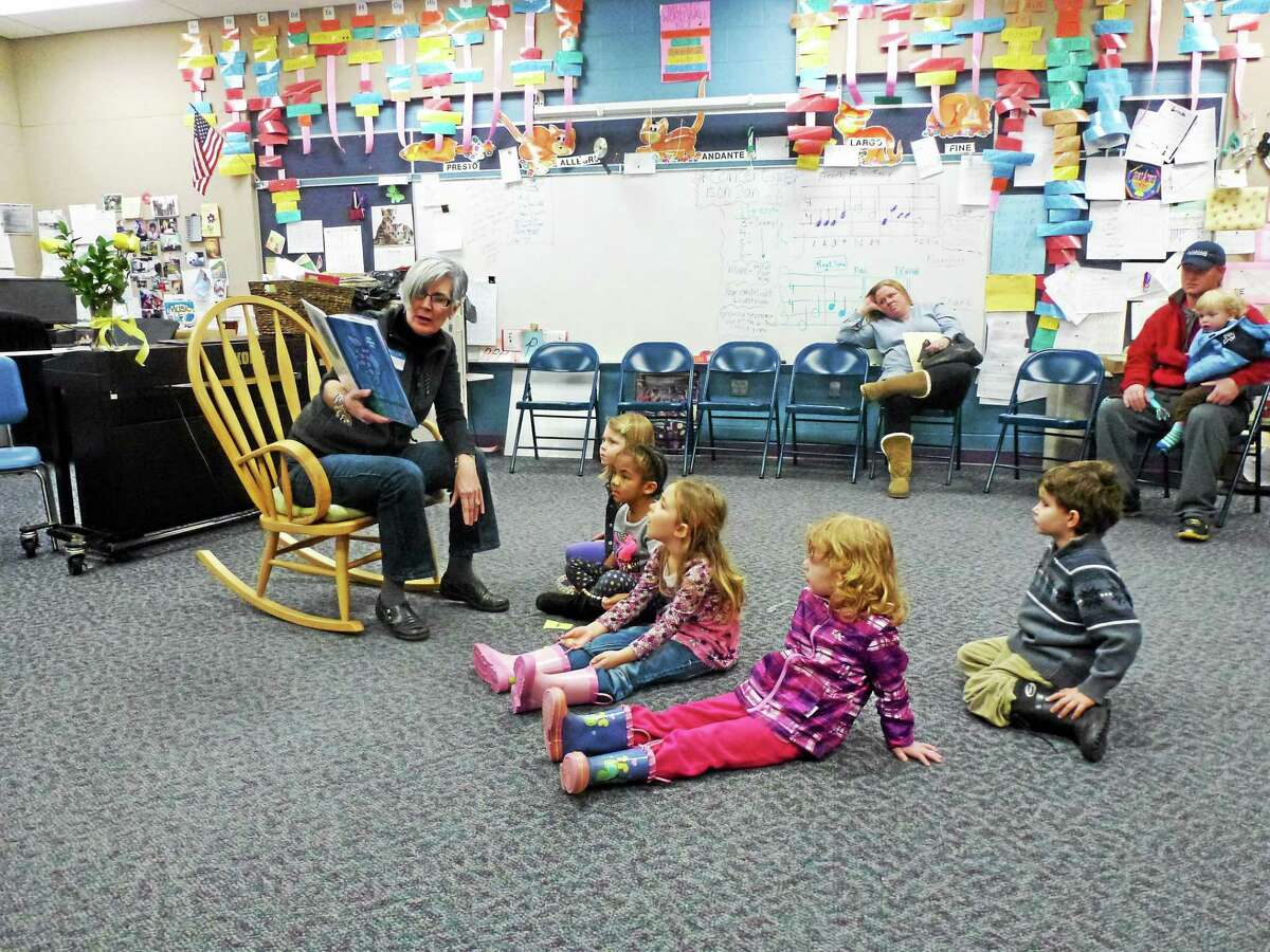 "Former Torrington kindergarten teacher and current first grade teacher Lucille Fines reads ""The Rainbow Fish"" to local children."