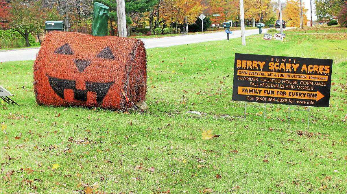 A sign for the Ruwet Berry Scary Acres sits near the intersection of Torringford Street and East Pearl Road in Torrington Friday.