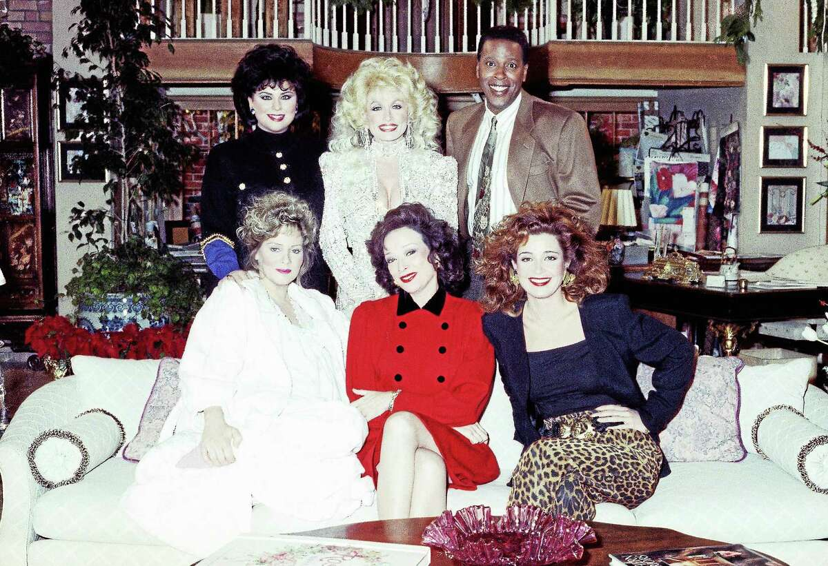 Singer and actress Dolly Parton, top center, joins the cast of ìDesigning Womenî for the New Yearís Day episode of the show airing on CBS, taping at the Burbank Studios on Dec. 8, 1989 in Burbank, Calif. Flanking Parton from left are show costars Delta Burke and Meshach Taylor with seated left to right, Jean Smart, Dixie Carter and Annie Potts.