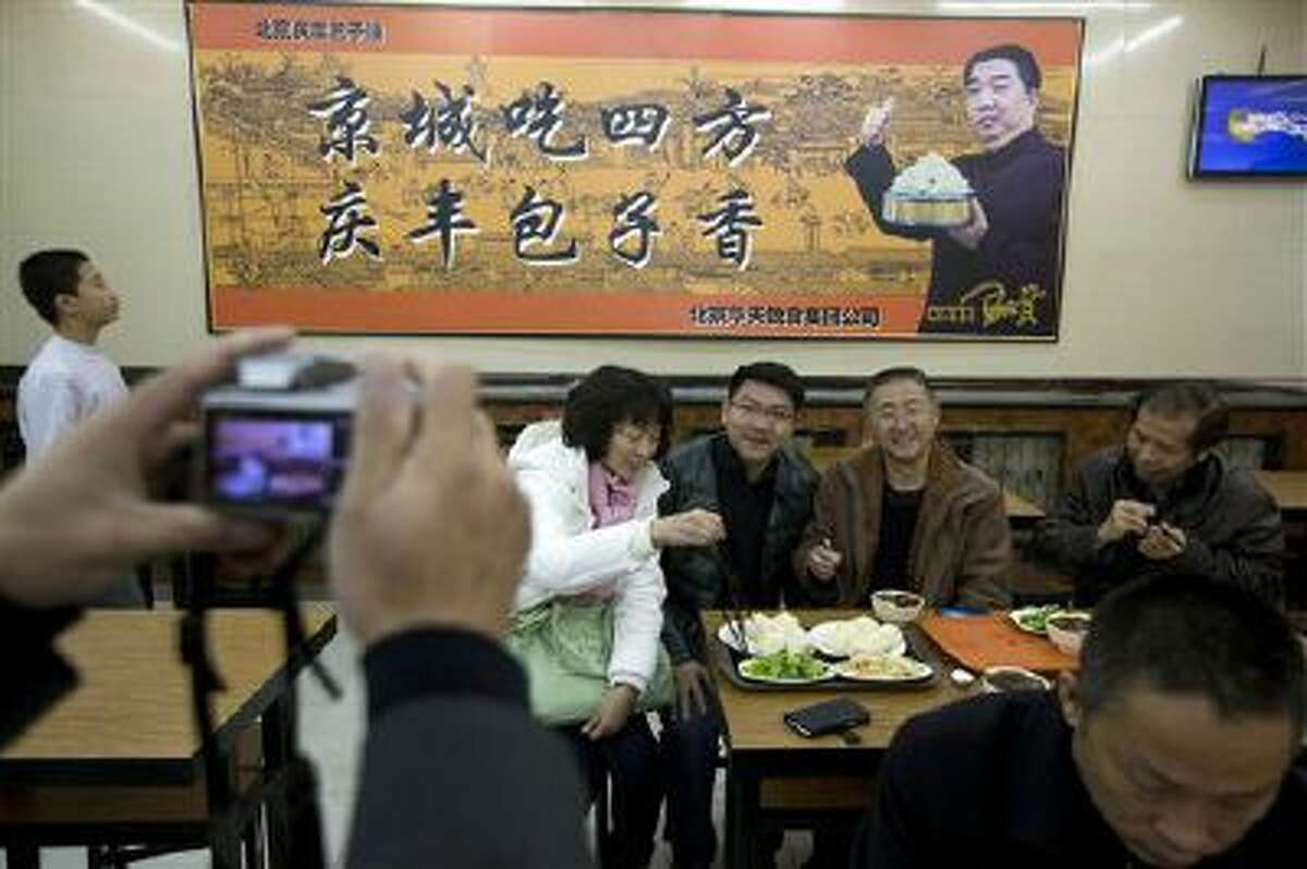 Tourists from Guangdong province, who ordered similar food to what Chinese President Xi Jinping ate the day before, pose for photos at the Qing-Feng Steamed Dumpling Shop in Beijing, China.