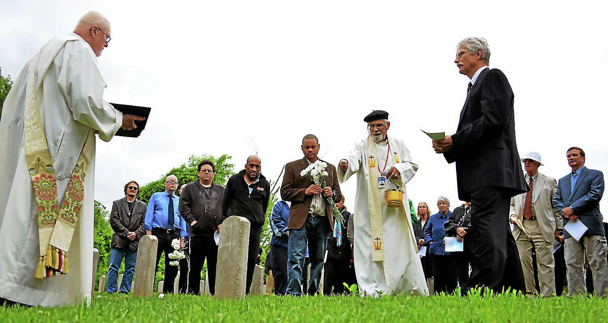 In this May 28, 2014 photo, the Rev. Josef Herz, center, chaplain at Connecticut Valley Hospital, blesses a grave during the annual ceremony to remember former mental patients at the hospital who are buried in its cemetery in Middletown, Conn.