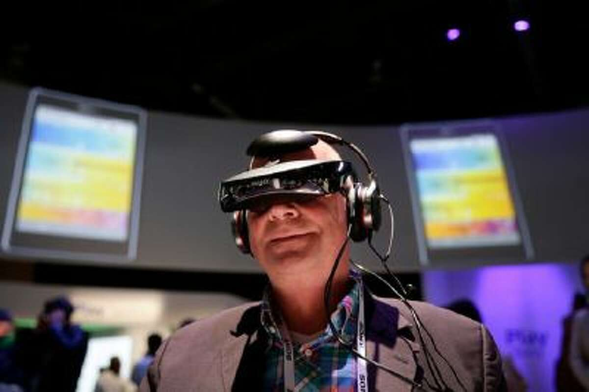 Juergen Boyny, of Germany, watches a video clip with a personal viewing device at the Sony booth at the International Consumer Electronics Show(CES) on Thursday, Jan. 9, 2014, in Las Vegas.