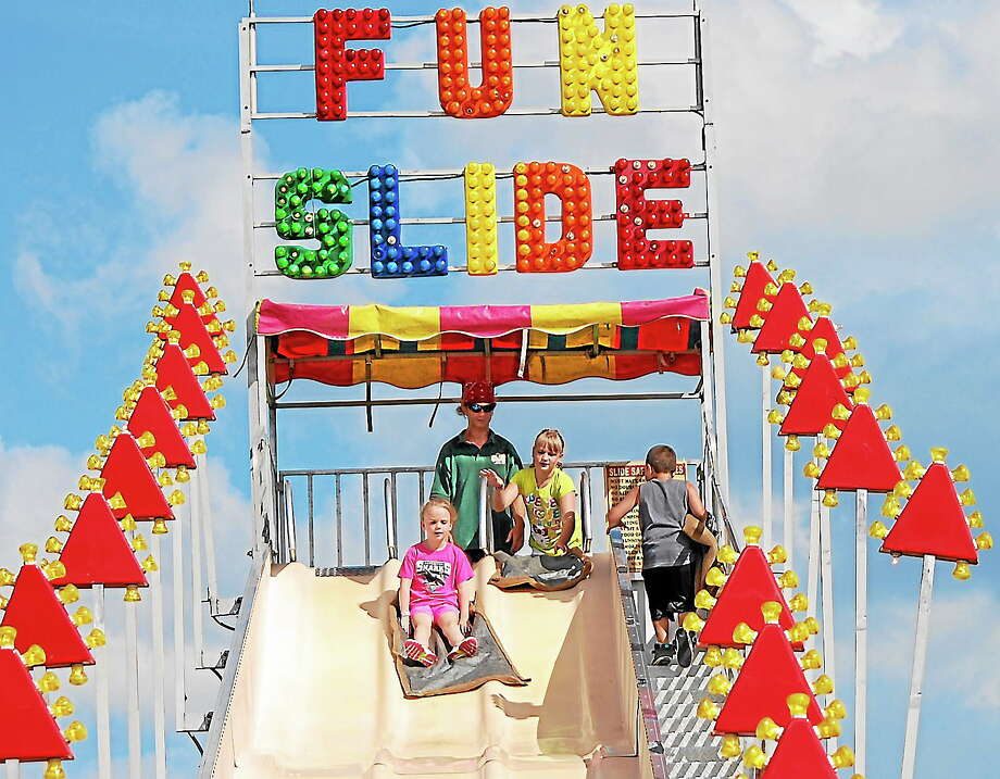 Brooke Fallon, left, heads down the Fun Slide, followed by her sister, Emma, center, during last year's Independence Day carnival at Torrington Middle School. Photo: Register Citizen File Photo
