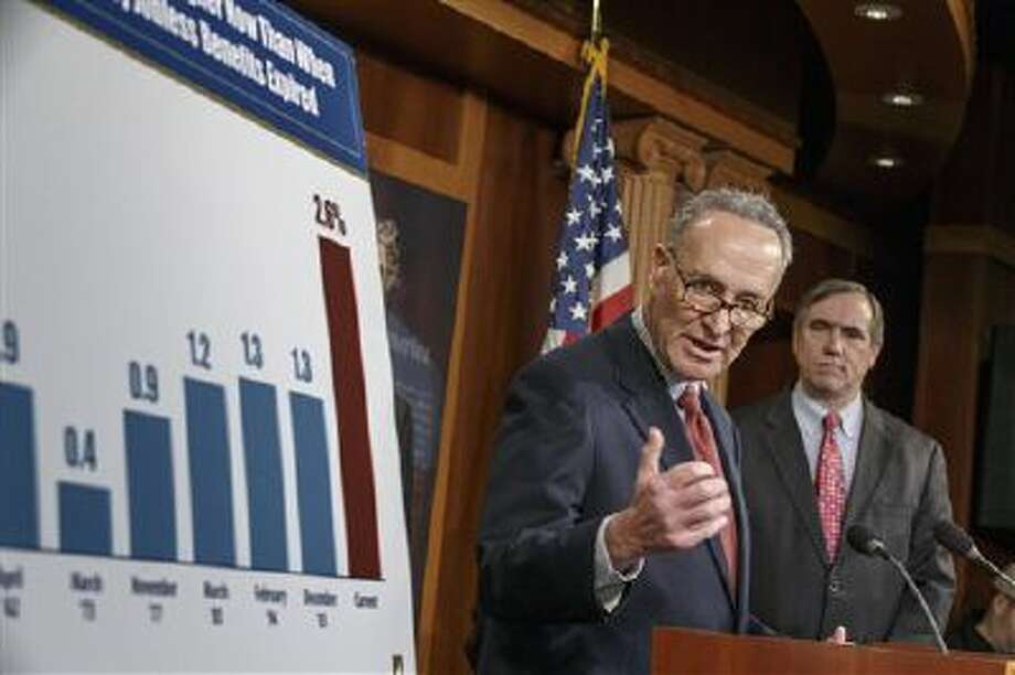 Sen. Charles Schumer, D-N.Y., joined at right by Sen. Jeff Merkley, D-Ore., meets with reporters after legislation to renew jobless benefits for the long-term unemployed unexpectedly cleared an initial Senate hurdle on Tuesday. Photo: AP / AP
