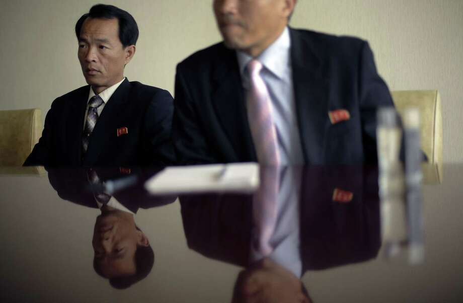 Ri Kyong Chol, left, and Sok Chol Won, right, professors from the Academy of Social Sciences, speak during an interview with the Associated Press, Thursday, Oct. 23, 2014, in Pyongyang, North Korea. The professors said the United States must make a formal apology to secure the freedom of two Americans who remain imprisoned in North Korea after the release this week of Jeffrey Fowle. (AP Photo/Wong Maye-E) Photo: AP / AP