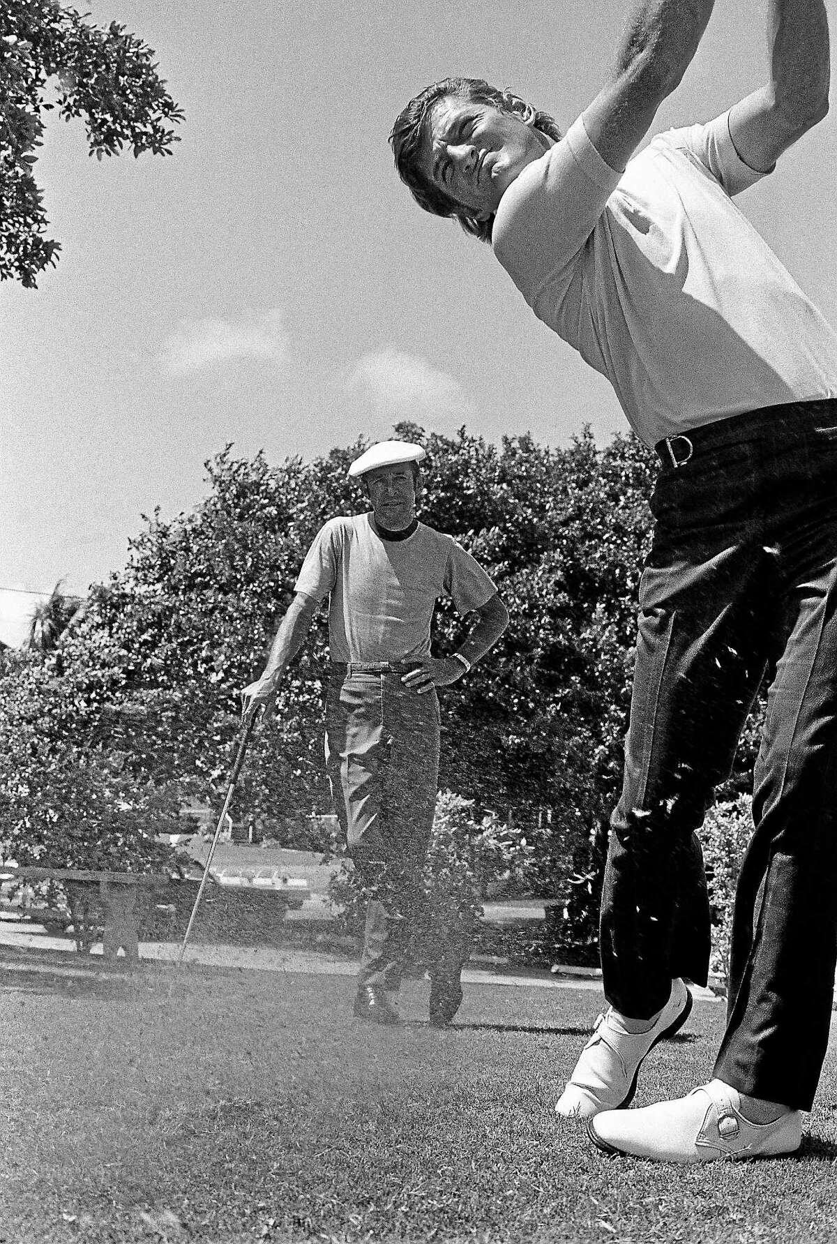 """Former major league outfielder, and current Chicago White Sox broadcaster, Ken """"Hawk"""" Harrelson follows through on his swing while his teacher, Bob Toski, look on during a practice session in September 1971. Ken Duke, the 2013 Travelers Championship winner, is a current pupil of the 87-year-old Toski, who recently returned to the scene of his 1953 Insurance City Open tournament victory."""
