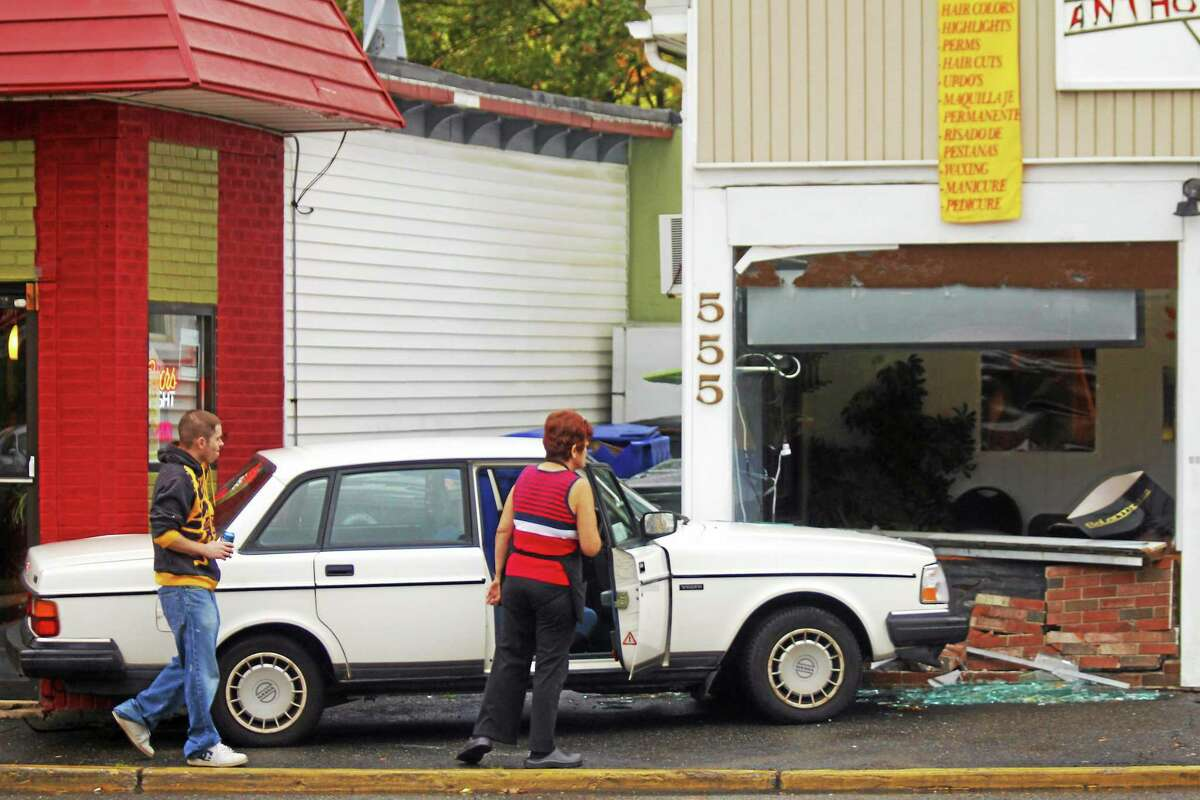 Onlookers gaze on the scene of an accident which involved a car crashing into Anthony's Barber Shop on Main Street Thursday in Torrington. No one was injured in the accident.