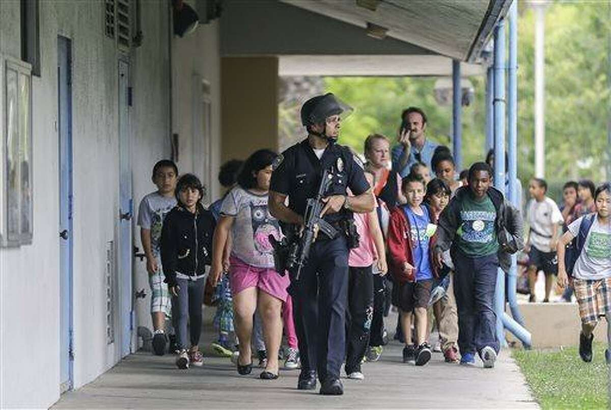 A Santa Monica police officer leads children on a field trip from Citizens of the World Charter School in Los Angeles out of Santa Monica College, where they had gone for a planetarium show, following a shooting in the area, in Santa Monica, Calif., Friday, June 7, 2013. Two people were found dead Friday in a burned home near the campus, where someone sprayed a street corner with gunfire. (AP Photo/Reed Saxon)