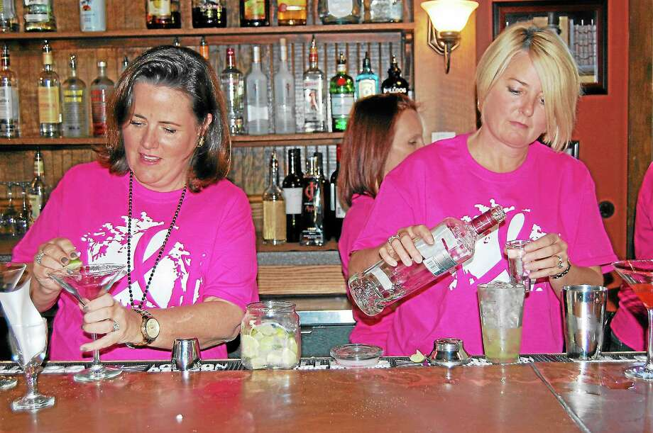 """Litchfield resident Kristen Arnold, right, and Nadine Keller, of Goshen, prepare drinks at the Litchfield Salt Water Grille on Sunday during """"Guest Bartender Night,"""" an event that supported Making Strides Against Breast Cancer. Photo: Photos By Mercy Quaye — Register Citizen"""