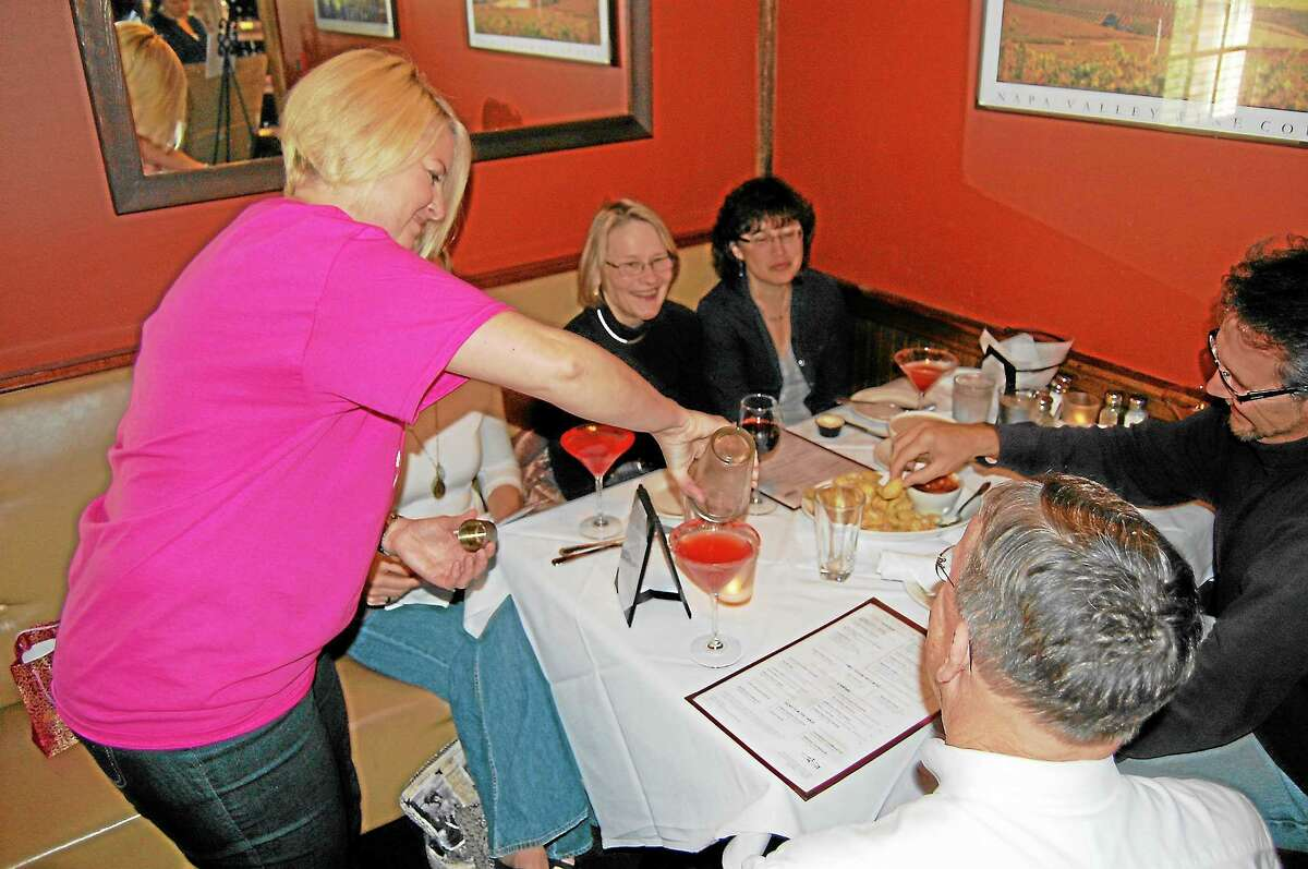 """Kristen Arnold, of Litchfield, serves drinks to a table at the Salt Water Grille on Sunday as part of """"Guest Bartender Night,"""" a benefit in support of breast cancer research and awareness."""