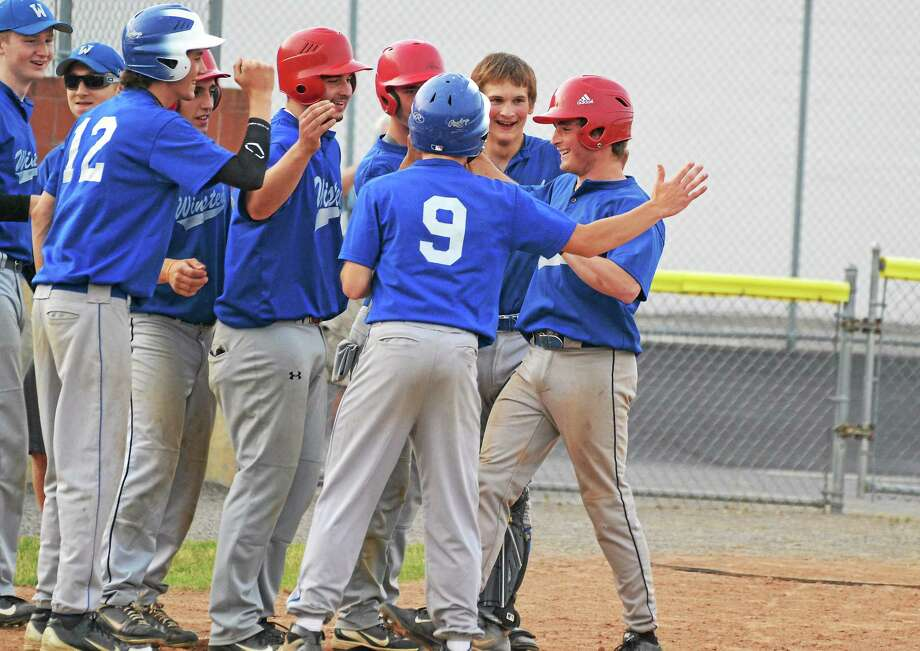 Winsted's Eddie Eseppi is greeted at home plate by his teammates, after hitting a grand slam in the second inning of Winsted's 5-3 win over Torrington. Photo: Pete Paguaga — Register Citizen