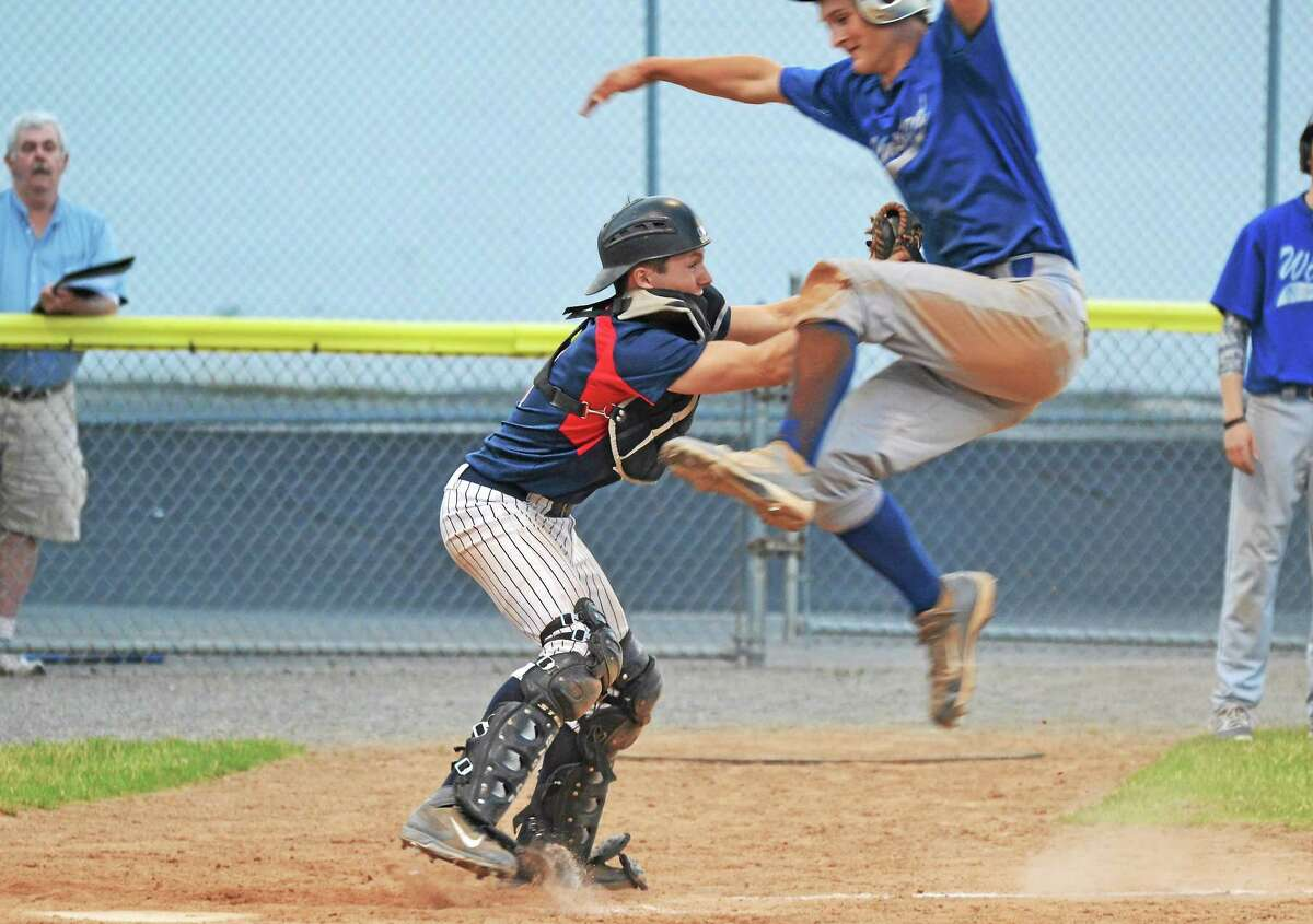 Torrington's Ben Thompson tags out Ryan Reynolds, as he tries to jump over him to score.