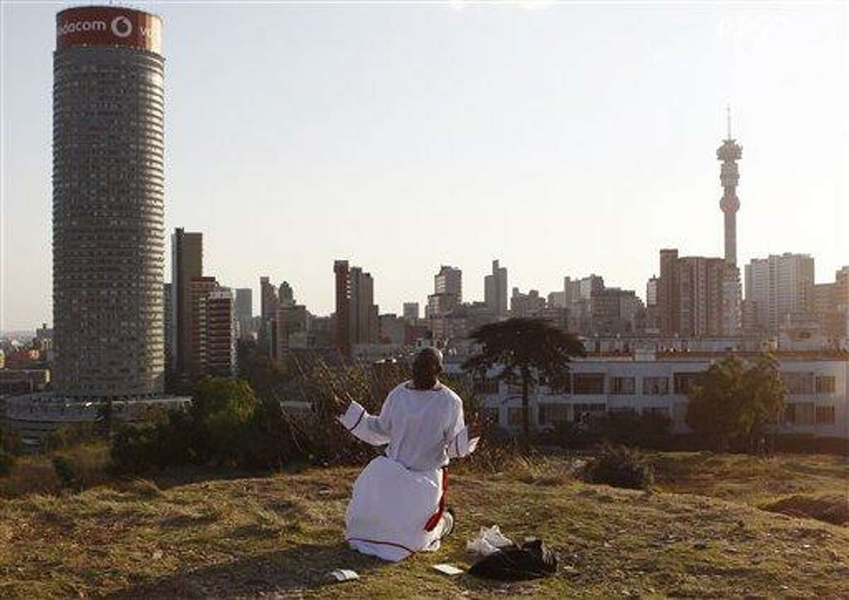 """A worshipper offers weekend prayers as vraious church groups offered weekend prayers for former president Nelson Mandela on a hill overlooking the city in Johannesburg, Saturday, June 8, 2013. Mandela is in """"serious but stable"""" condition after being taken to a hospital to be treated for a lung infection, the government said, prompting an outpouring of concern from admirers of a man who helped to end white racist rule. (AP Photo/Denis Farrell)"""