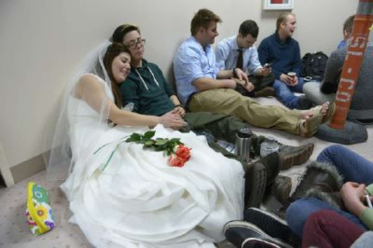In this Dec. 22, 2013, file photo, Heather, left, and Jax Collins of West Jordan join hundreds of other same-sex couples descending on county clerk offices around the state of Utah including the Salt Lake County office to request marriage licenses.