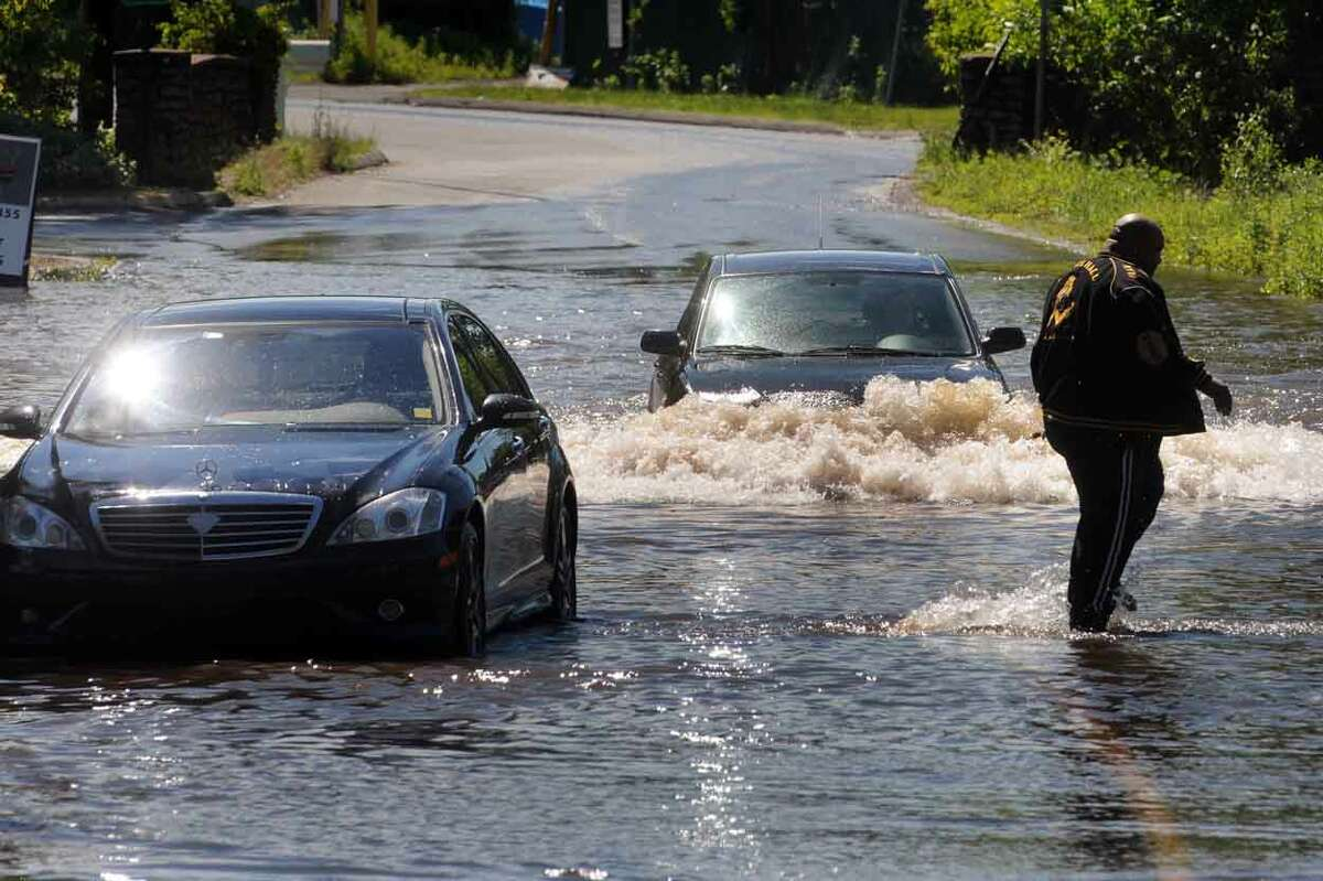 A motorist walks away from his car after stalling it out on a water covered portion of School ground Rd in Branford following last nights torrential rain. 06.08.13 vm Williams