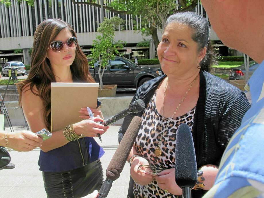 Juror Earlanne Leslie, center, speaks to reporters in Honolulu on Friday, June 27, 2014 after the jury she served on said it was deadlocked on whether a former Army soldier should be sentenced to death for killing his 5-year-old daughter in Hawaii's first death penalty trial since its statehood. A federal judge will sentence Naeem Williams to life in prison without the possibility of release. (AP Photo/Audrey McAvoy) Photo: AP / AP