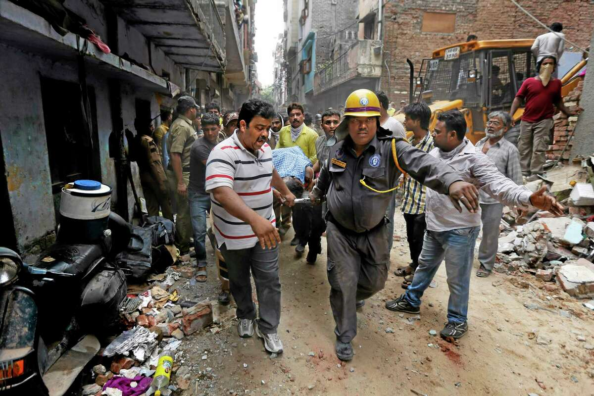 EDS NOTE: GRAPHIC CONTENT - Rescue workers carry the body of a victim amid the debris of a building that collapsed in New Delhi, India, Saturday, June 28, 2014. A dilapidated building collapsed in the Indian capital on Saturday, killing at least seven people as rescuers searched for others believed to be trapped. (AP Photo/Altaf Qadri)