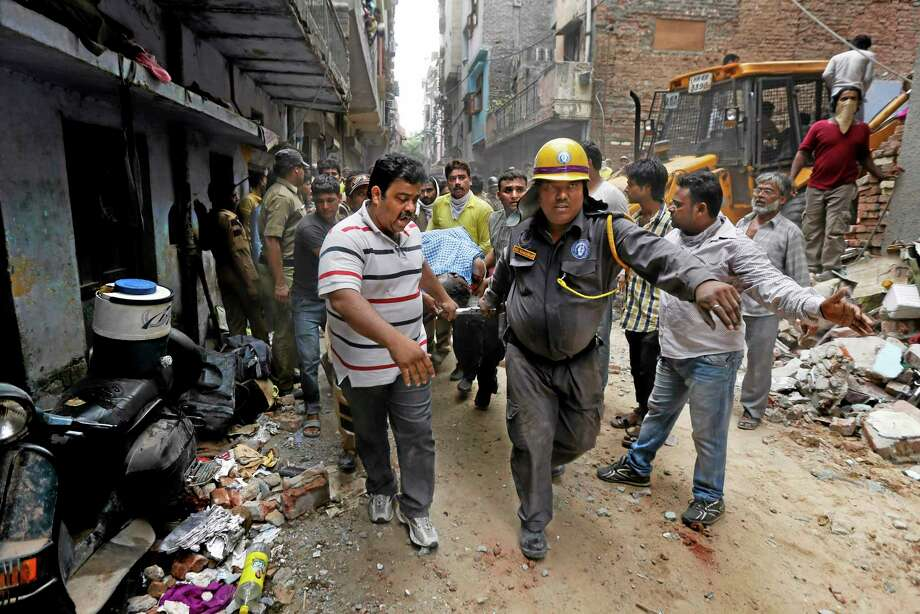 EDS NOTE: GRAPHIC CONTENT - Rescue workers carry the body of a victim amid the debris of a building that collapsed in New Delhi, India, Saturday, June 28, 2014. A dilapidated building collapsed in the Indian capital on Saturday, killing at least seven people as rescuers searched for others believed to be trapped. (AP Photo/Altaf Qadri) Photo: AP / AP