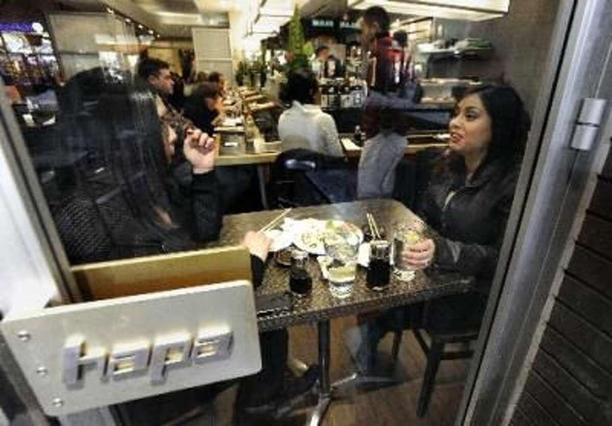 Janae Bacca, at left, and her sister Devon Bacca enjoy some dinner together at Hapa Sushi in Boulder, Colo.