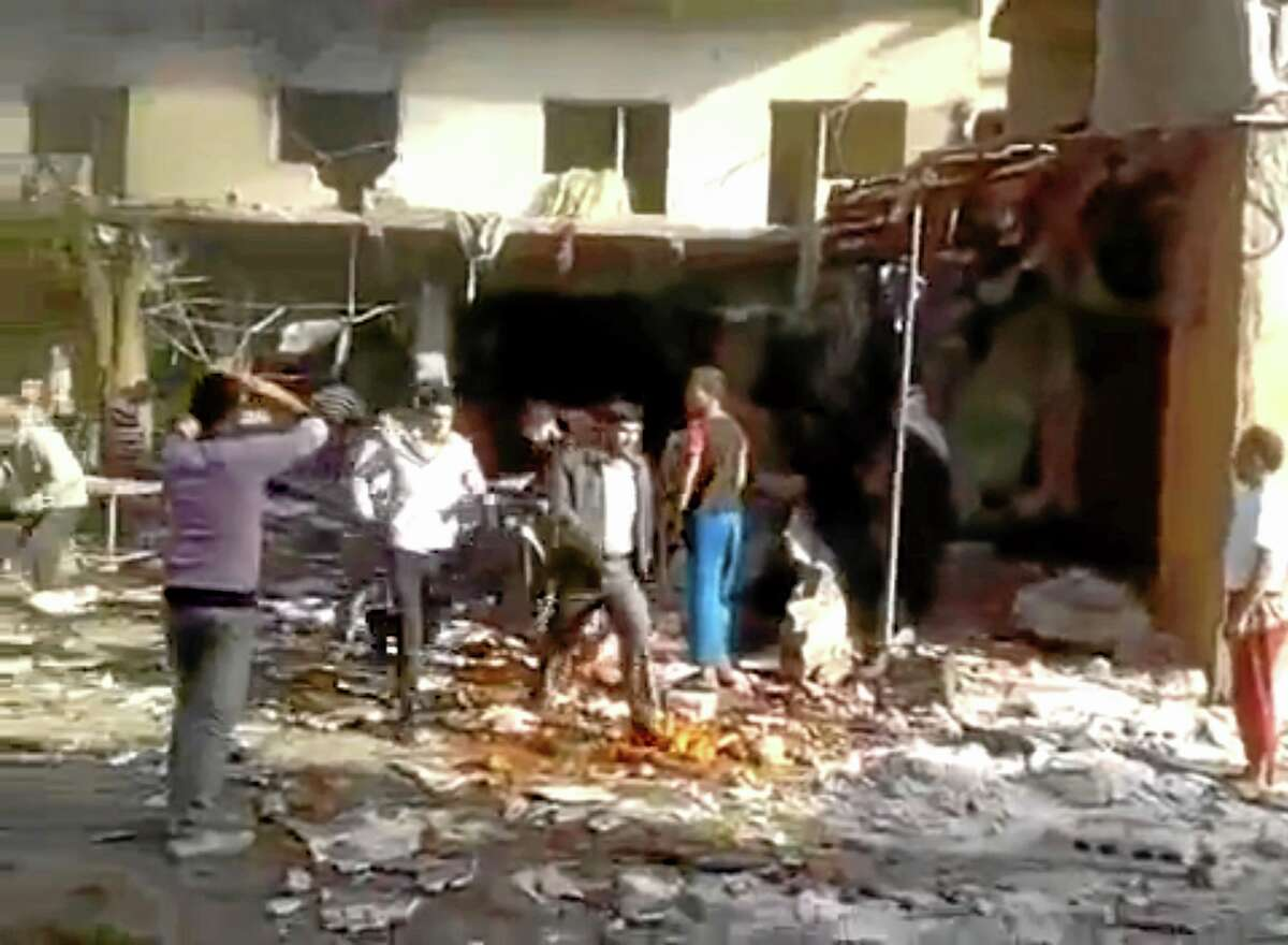 This image made from citizen journalist video posted by the Shaam News Network, which is consistent with other AP reporting, shows people evacuating a victim of a car bomb attack on a market in the town of Darkoush in Idlib province, Monday, Oct. 14, 2013. Syrian activist groups say the bombing in a rebel-held northwestern town has killed and wounded dozens of people. Car bombs are becoming more common in Syria's civil war, now in its third year. The conflict has killed more than 100,000 people.(AP Photo/Shaam News Network via AP video)