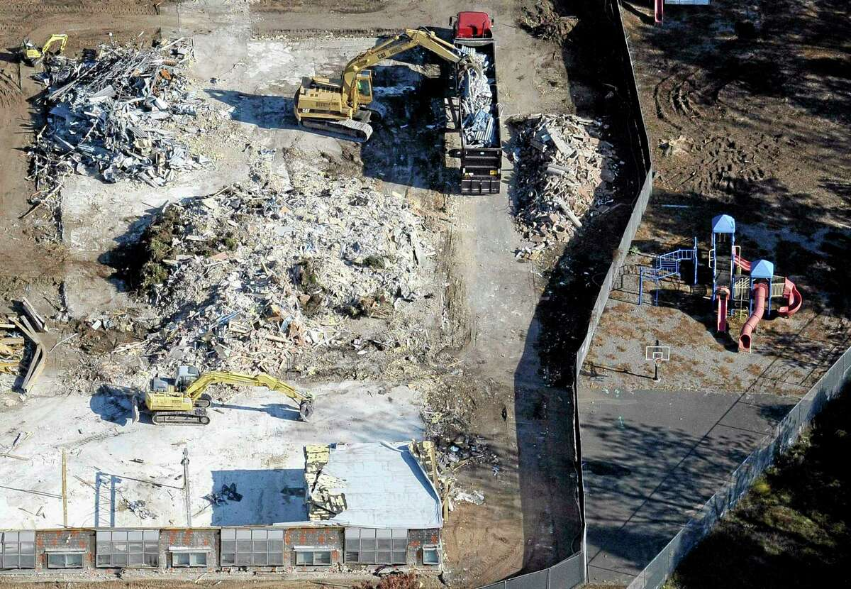 FILE - In this Oct. 28, 2013 aerial file photo, workers use backhoes to remove rubble during the demolition of Sandy Hook Elementary School in Newtown, Conn., where gunman Adam Lanza killed 20 children and six adult educators on Dec. 14, 2012. (AP Photo/Jessica Hill, File)