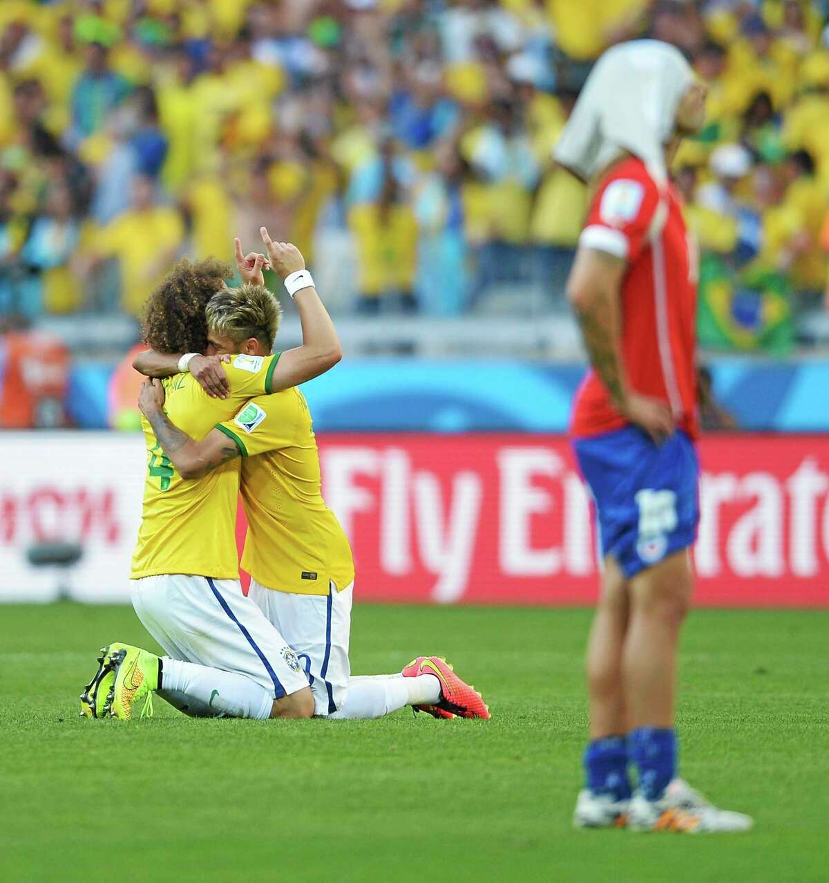 Brazil's David Luiz, left, and Neymar hug after a penalty shootout following regulation time during the World Cup Round of 16 match against Chile Saturday at the Mineirao Stadium in Belo Horizonte, Brazil.