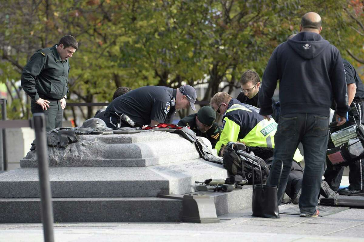 Emergency personnel tend to a soldier shot at the National Memorial near Parliament Hill in Ottawa on Wednesday Oct. 22, 2014. The soldier was standing guard when an unknown gunman shot him.