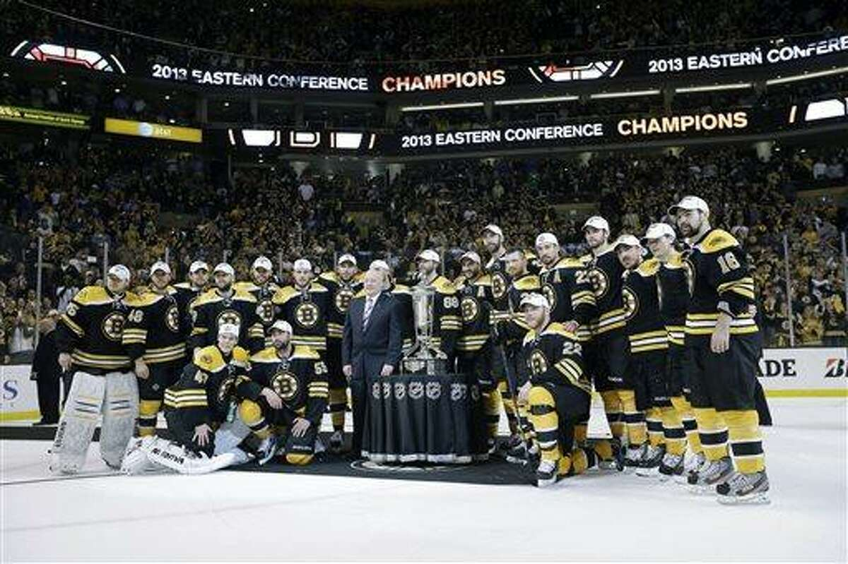 The Boston Bruins pose with the trophy after beating the Pittsburgh Penguins 1-0 in Game 4 of the Eastern Conference finals of the NHL hockey Stanley Cup playoffs, in Boston on Friday, June 7, 2013. The Bruins advanced to the Stanley Cup finals. (AP Photo/Elise Amendola)