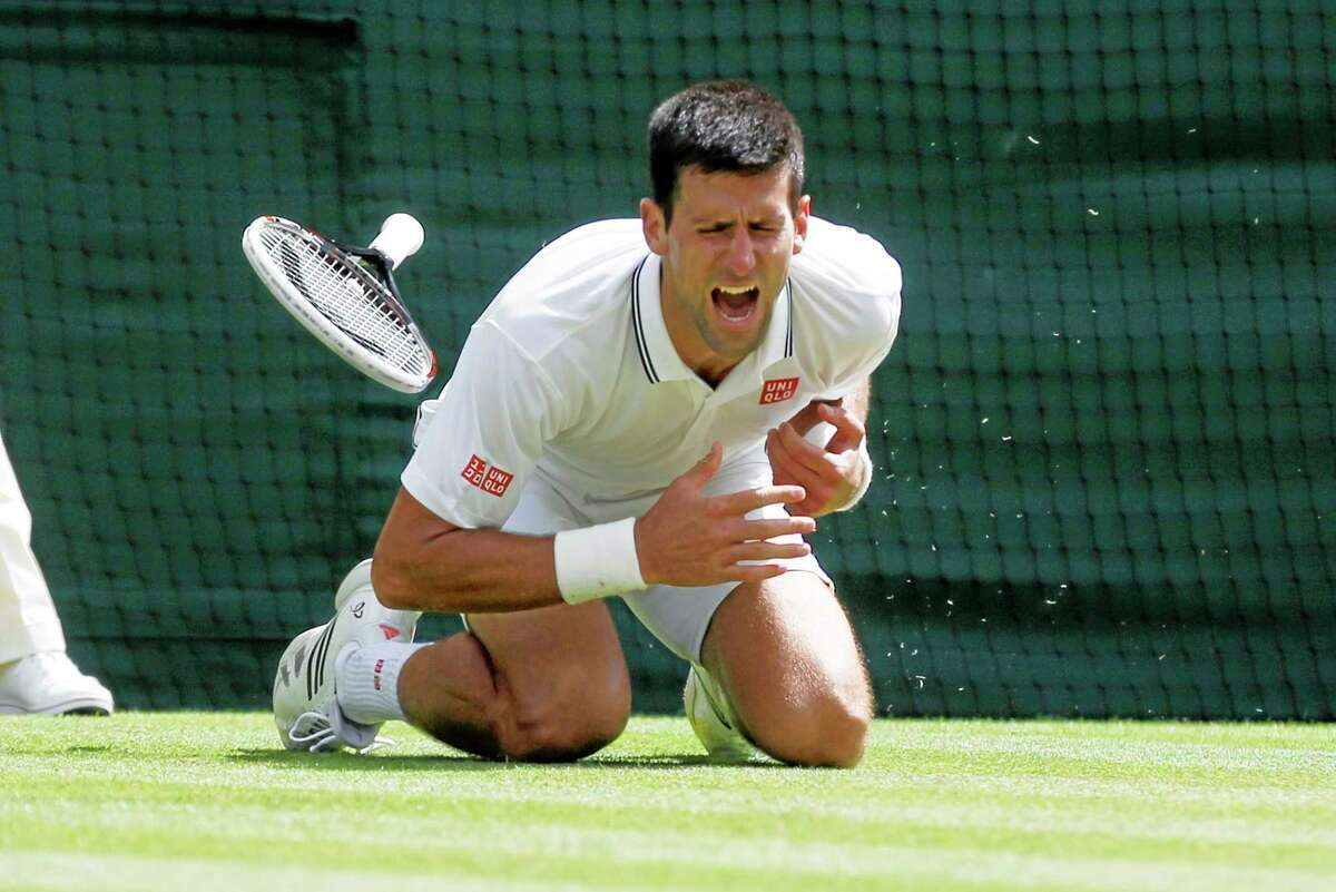 Novak Djokovic shouts in pain after falling onto the court during his match against Gilles Simon Friday at the All England Lawn Tennis Championships in Wimbledon, London.