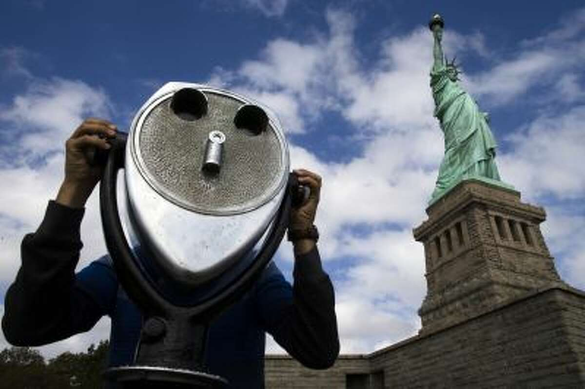 The Statue of Liberty looms over a visitor as he uses binoculars to look out onto New York Harbor, Sunday, Oct. 13, 2013, in New York. The Statue of Liberty reopened to the public after the state of New York agreed to shoulder the costs of running the site during the partial federal government shutdown. (AP Photo/John Minchillo)
