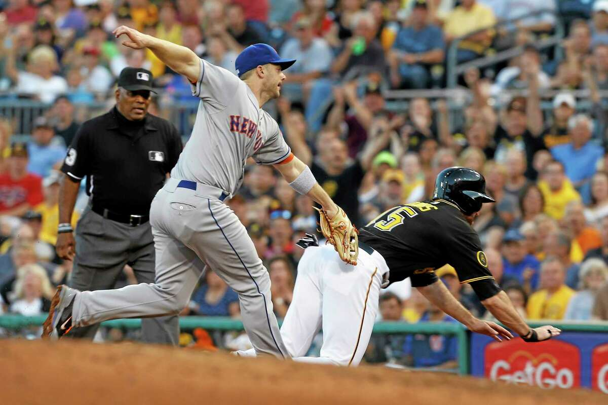 The Pirates' Ike Davis, right, dives for the bag as New York Mets third baseman David Wright tags him out in the fourth inning of Thursday's game in Pittsburgh.