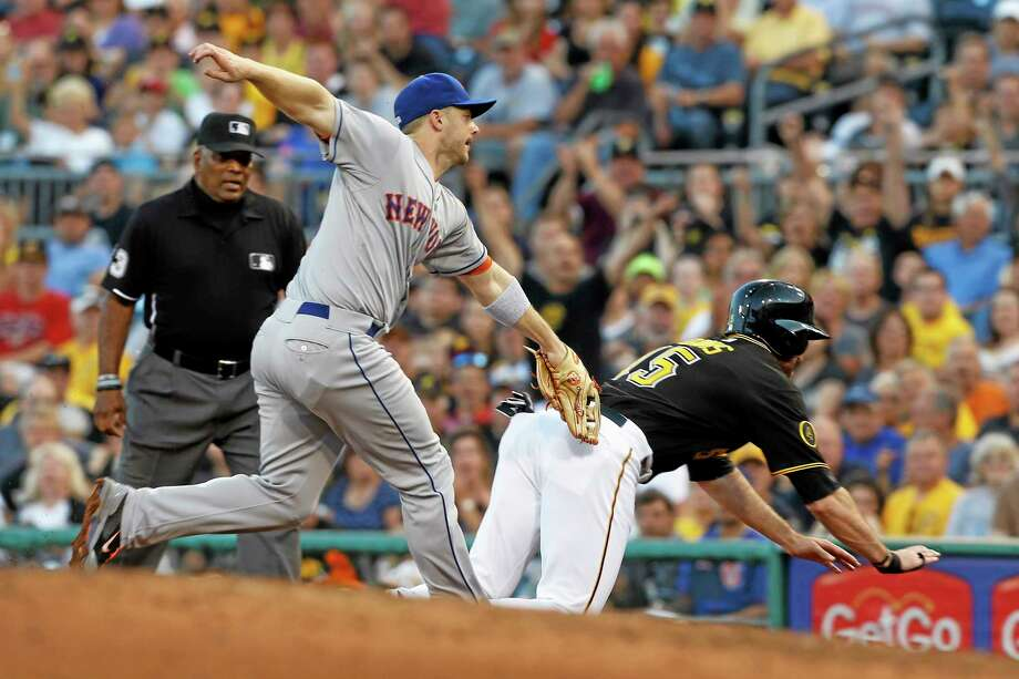 The Pirates' Ike Davis, right, dives for the bag as New York Mets third baseman David Wright tags him out in the fourth inning of Thursday's game in Pittsburgh. Photo: Keith Srakocic — The Associated Press  / AP