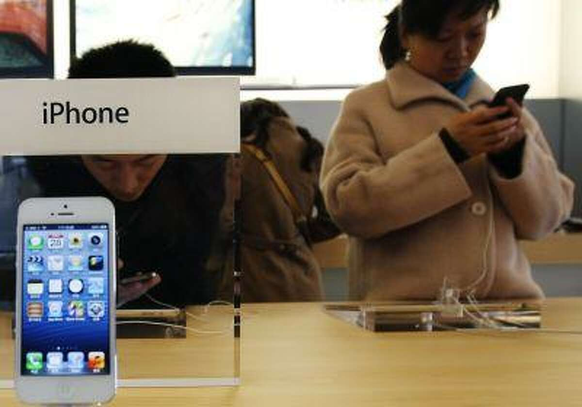 Visitors try the iPhone at an Apple Store in Beijing.