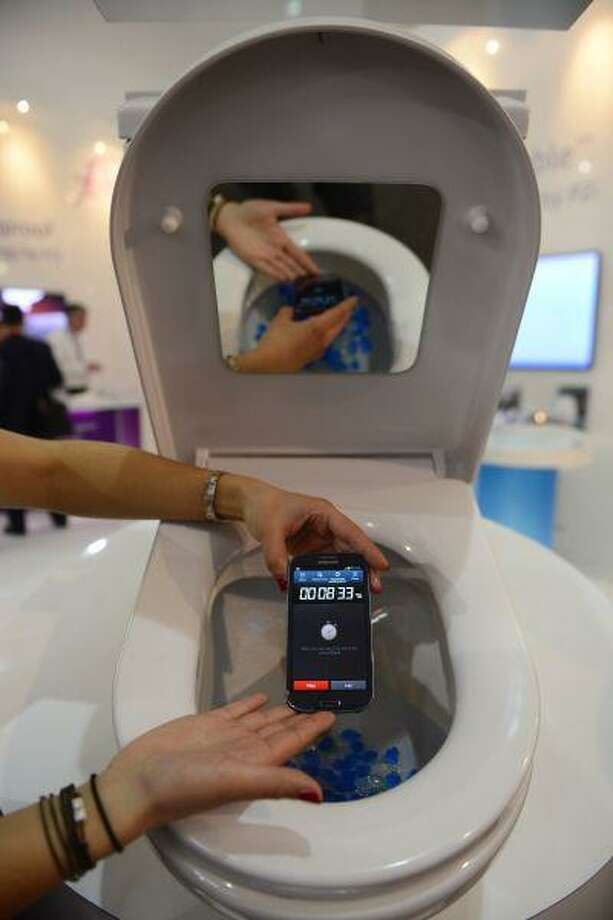 "A woman uses a phone which is protected by the ""P2i perform protect improve"" system inside a toilet bowl at a demonstration of the system at the Mobile World Congress, the world's largest mobile phone trade show, in Barcelona, Spain, Wednesday, Feb. 27, 2013. (AP Photo/Manu Fernandez) Photo: ASSOCIATED PRESS / AP2013"