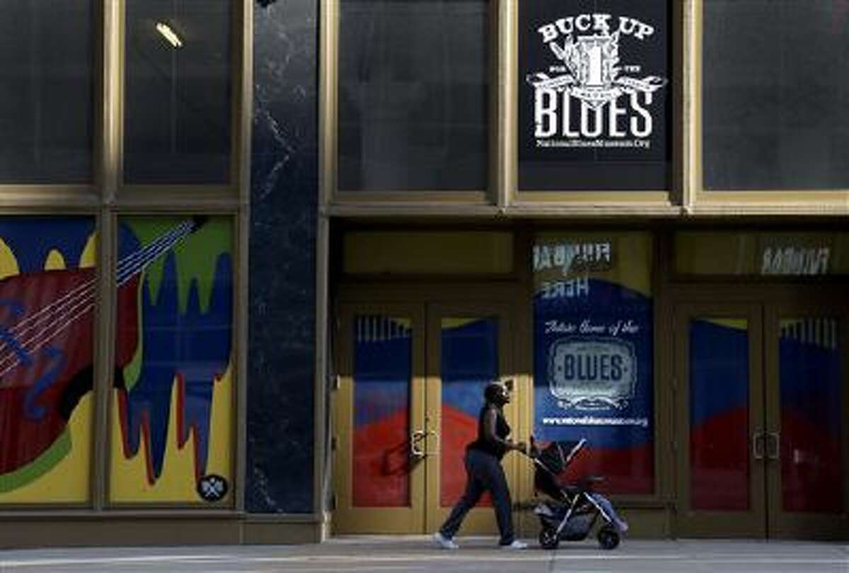 A woman pushes a stroller past the site of the National Blues Museum, set to open next year, in St. Louis. Casual Blues fans may not immediately think of St. Louis when considering the genre, but organizers of the project say the city has its own rich musical history making it a deserving home for the national museum.