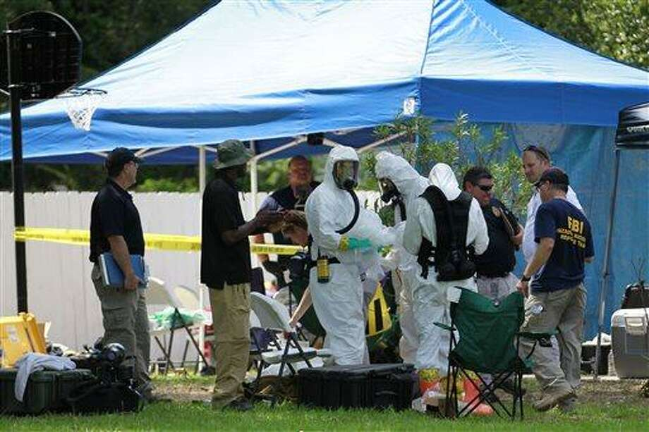 FILE - In this May 31, 2013 file photo, members of an FBI hazardous materials team prepare to enter a residence in New Boston, Texas in connection with a federal investigation surrounding ricin-laced letters mailed to President Barack Obama and New York Mayor Michael Bloomberg. Two U.S. law enforcement officials say Shannon Richardson of New Boston, Texas, has been arrested Friday, June 7, in the investigation. (AP Photo/Texarkana Gazette, Evan Lewis, File) MANDATORY CREDIT Photo: AP / Texarkana Gazette