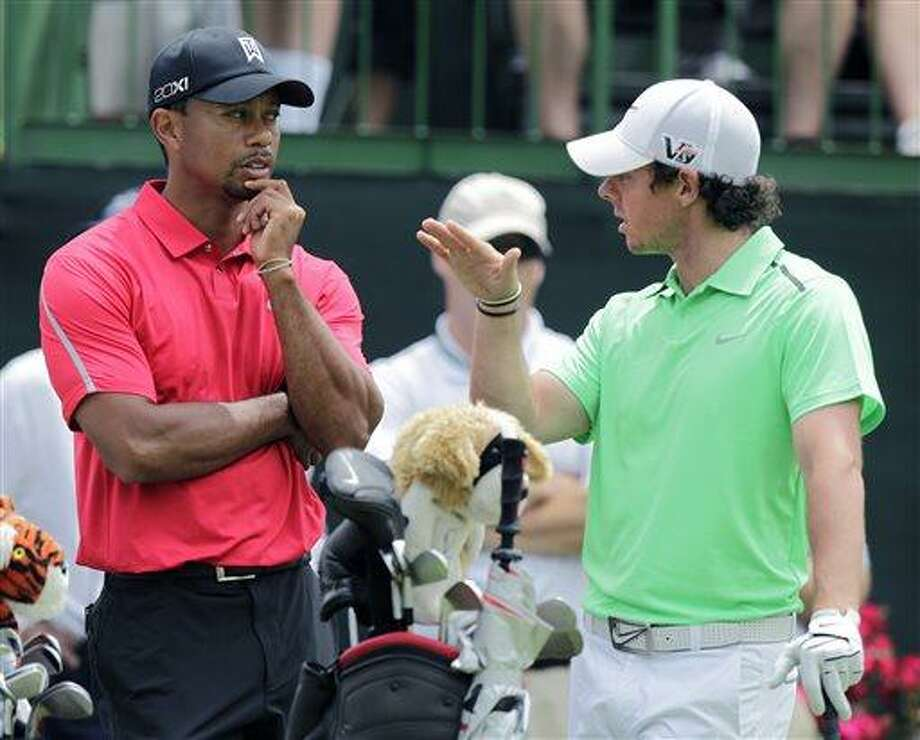 ADVANCE FOR WEEKEND EDITIONS, JUNE 8-9 - FILE - In this June 2, 2013, file photo, Tiger Woods, left, talks with Rory McIlroy, of Northern Ireland, as they wait to hit on the 12th hole during the final round of the Memorial golf tournament in Dublin, Ohio. Few other American courses have the kind of history found at Merion. They have red wicker baskets, the symbol of golf club, though its origins remain a mystery. Equally mysterious to Woods, McIlroy and the rest of the stars at the 113th U.S. Open is Merion itself.  (AP Photo/Jay LaPrete) Photo: AP / FR52593 AP