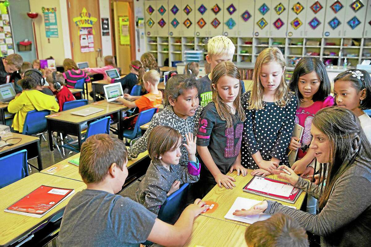 In this Oct. 9, 2013 photo, third grade teacher Janell Cooke talks with a group of students about a story they are working on as other students work on concentrated vocabulary at Tualatin Elementary in Tualatin, Ore.