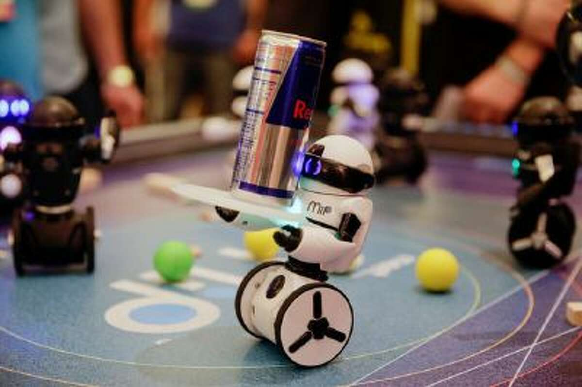 WowWee's MiP, a balancing robot that can be controlled by hand motions or smartphones, carries a can of energy drink at the International Consumer Electronics Show on Wednesday, Jan. 8, 2014, in Las Vegas.