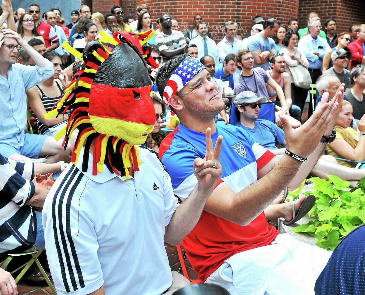 (Arnold Gold-New Haven Register) Jason Wright (left), born in Germany and living in New Haven, and Clayton Banks (center) of Derby watch Germany play the USA in a World Cup soccer match on 6/26/2014 with other fans in Pitkin Plaza in New Haven.