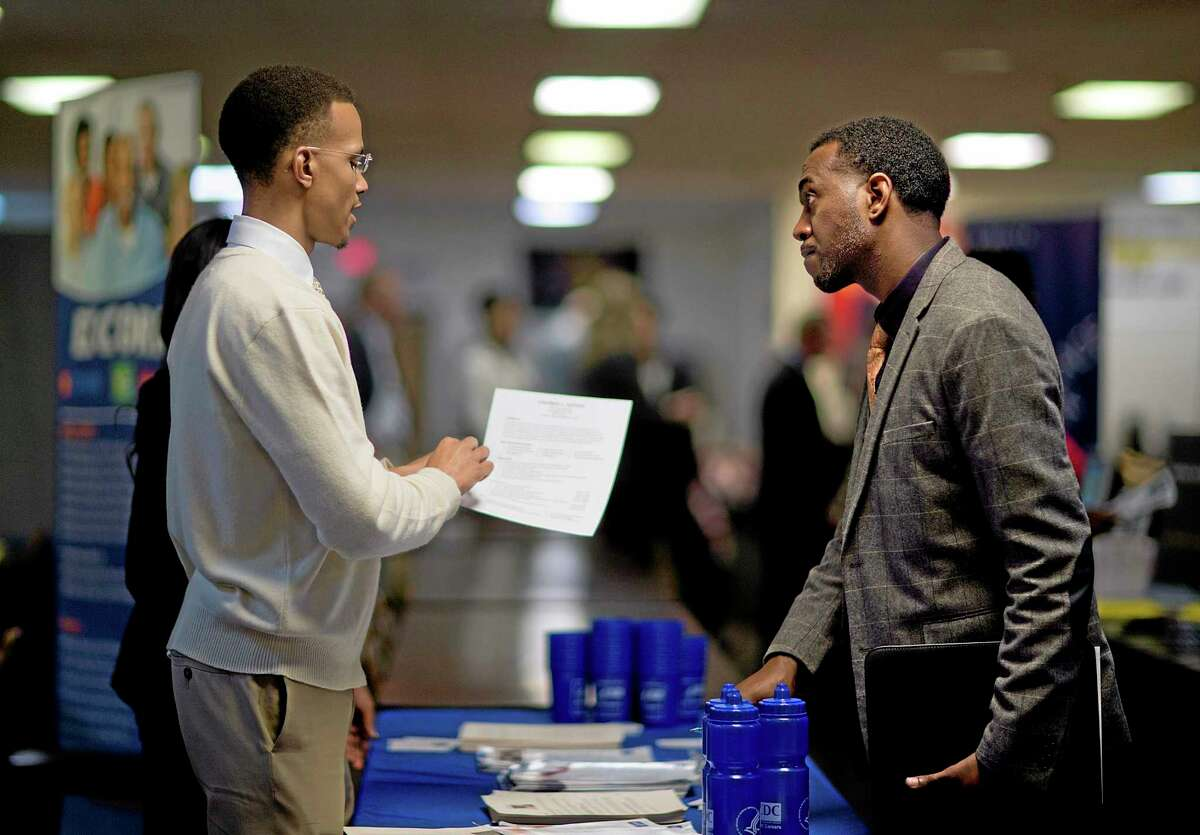 FILE - In this Thursday, Nov. 14, 2013, file photo, retired U.S. Air Force Master Sgt. Thomas Gipson, of Atlanta, right, has his resume looked over by Ralph Brown, a management and program analyst with the Centers for Disease Control and Prevention, during a job fair for veterans at the VFW Post 2681,Marietta, Ga. The Labor Department reports on the number of people who applied for U.S. unemployment benefits the first week of 2014 on Thursday, Jan. 9, 2014. AP Photo/David Goldman, File)
