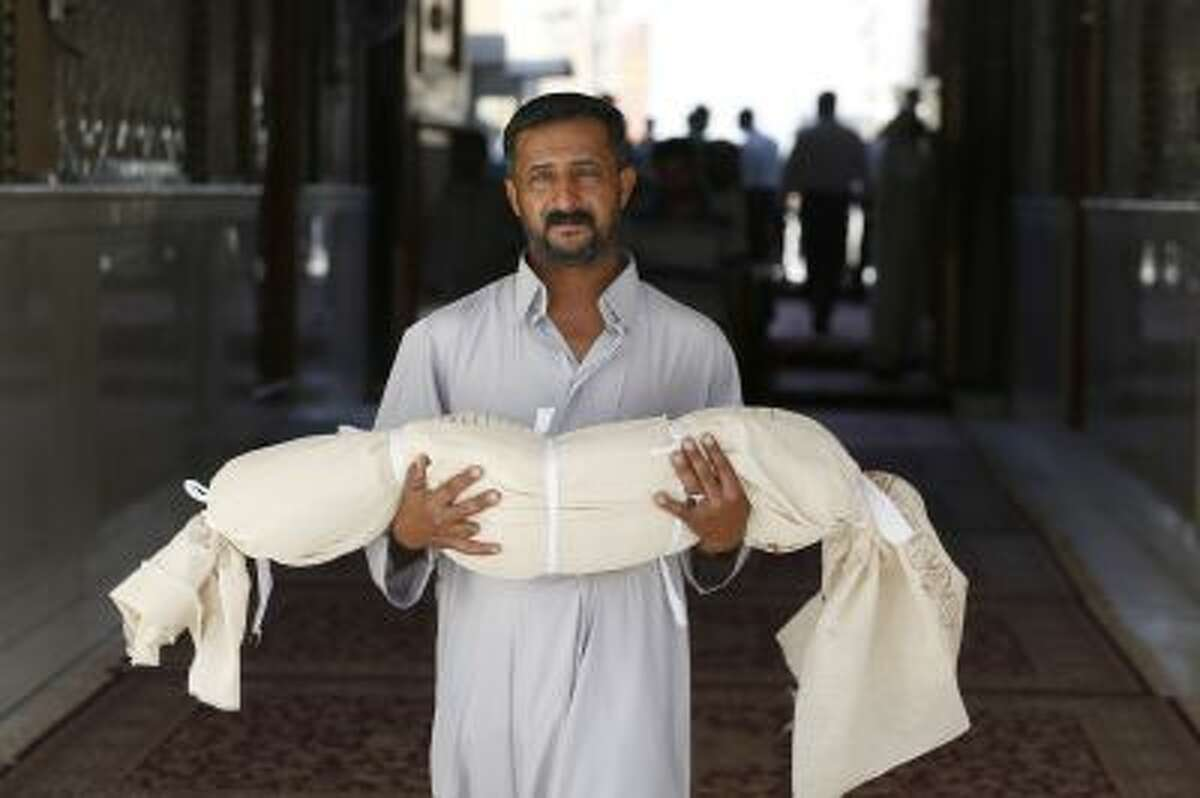 FILE - In this Tuesday, Sept. 24, 2013 file photo, Qasim Ahmed Tahan carries the dead body of his 5-year-old son, Walid, who was killed in a bombing on Monday, before burial in the Shiite holy city of Najaf, 100 miles south of Baghdad, Iraq, Tuesday, Sept. 24, 2013.