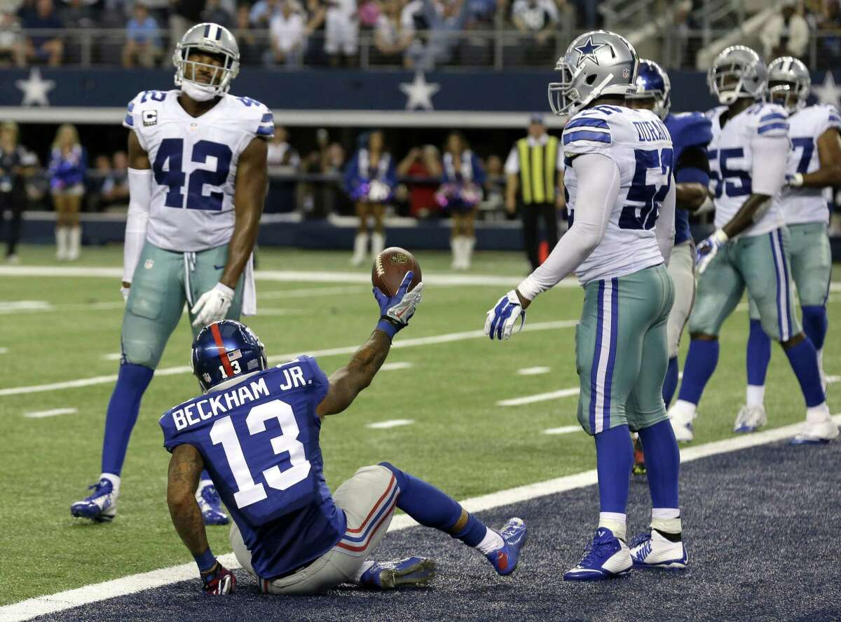 New York Giants rookie receiver Odell Beckham Jr. celebrates his touchdown reception in front of Dallas Cowboys defenders Barry Church (42) and Justin Durant (52) on Sunday in Arlington, Texas.